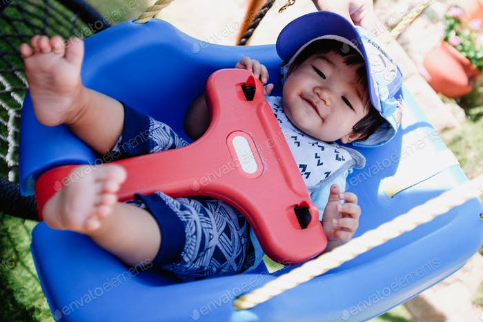 Diverse happy smiling cute little boy wearing hat on a swing at home