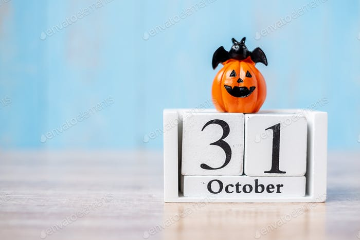 Happy Halloween day with 31 October calendar wood, jack o lantern pumpkin and bat decor