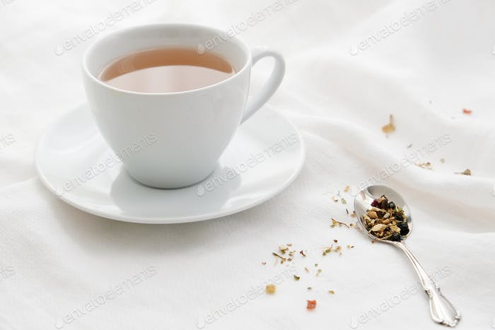 White teacup with tea on white linen with teaspoon and tea leaves