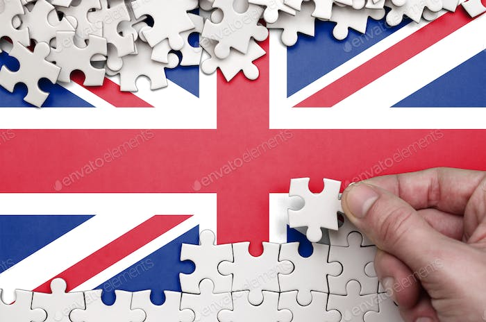 Great britain flag  is depicted on a table on which the human hand folds a puzzle of white color.