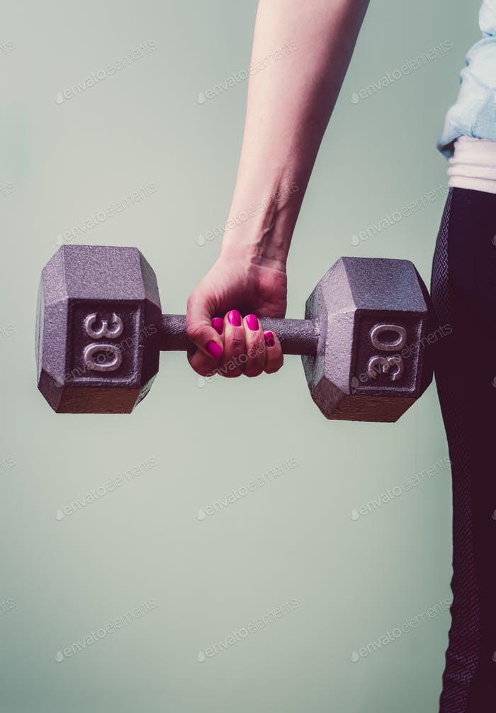 Woman with pink fingernails lifting a 30 pound dumbbell