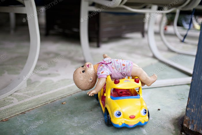 creepy doll lying on a toy school bus