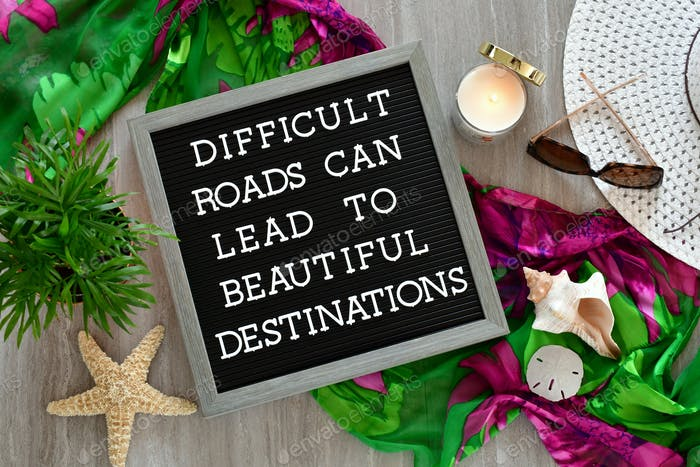 Difficult Roads Can Lead To Beautiful Destinations - message sign travel flat lay