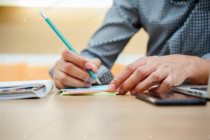 close up employee man writing short note memo on mini sticky pad for notice something after finish