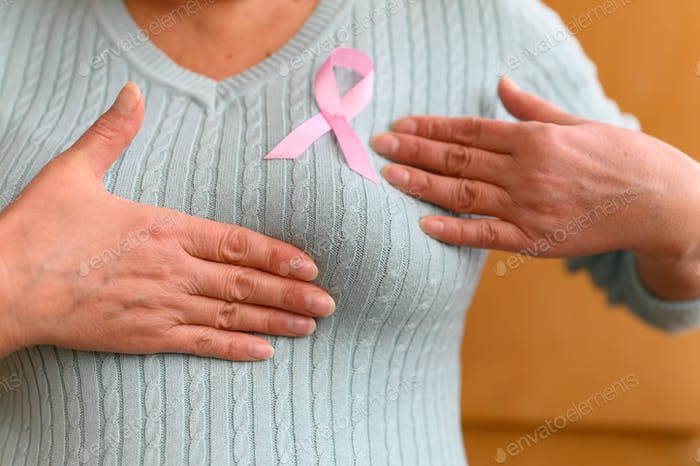 hands of a mature woman examine her breasts. a pink badge ribbon is attached to a knitted sweater