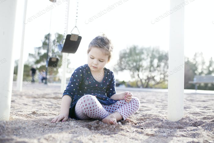 girl digging in sand at the playground
