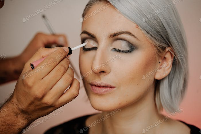 Makeup applications on the eyes of a woman with gray hair