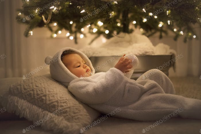 A toddler filled with wonder beneath the brightly lit Christmas tree.