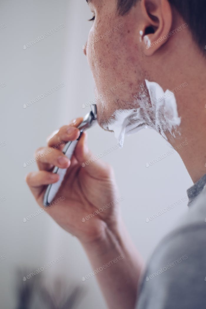 Young man shaving with a razor
