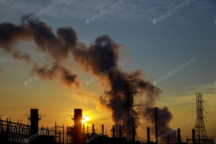 the sun rises over the coal power plant station on a bitterly cold morning.