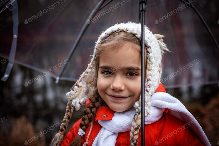 Happy pretty 7-8 years girl in red coat with transparent umbrella walking alone in early spring