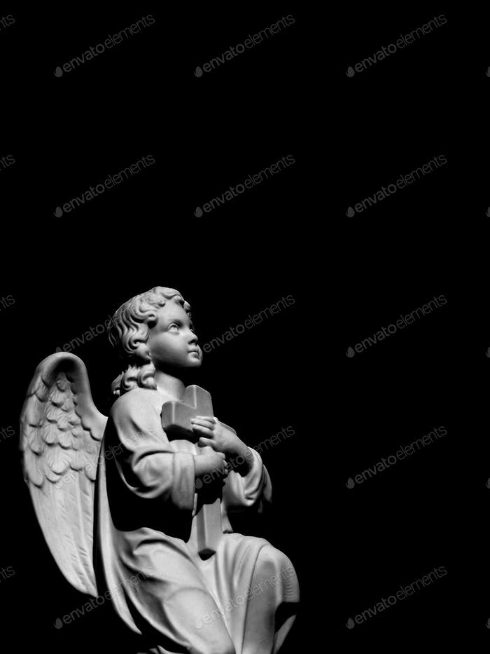 Statue of an angel holding a cross looking up to heaven