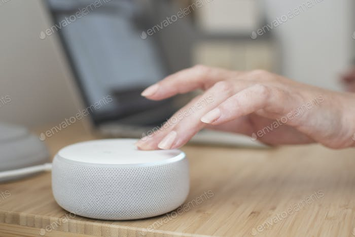 A woman's hand turns down the volume on an Amazon Alexa device