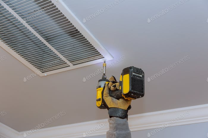Man is installing the ceiling vent cover for home heating and cooling system