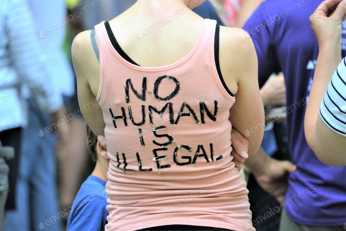 Millennial wearing a t-shirt at a protest rally!! No human is illegal