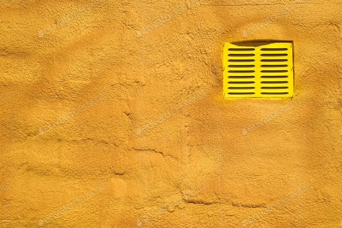 Yellow vent on a yellow brick wall