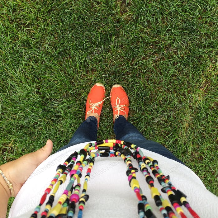 Selfie outfit of the day with colorful tribal necklace and orange shoes on green grass.