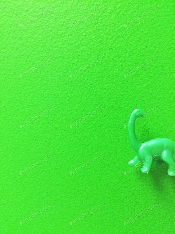 Green wall and green dinosaur