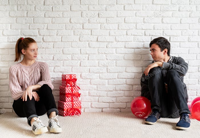 Young couple having problems or disagreements sitting away from each other