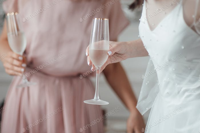 Two millennial candid lifestyle brunette girls in bridal outfits are having fun drinking champagne.