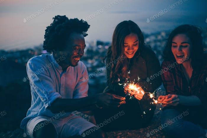 Millennial group of friends lighting sparklers at night