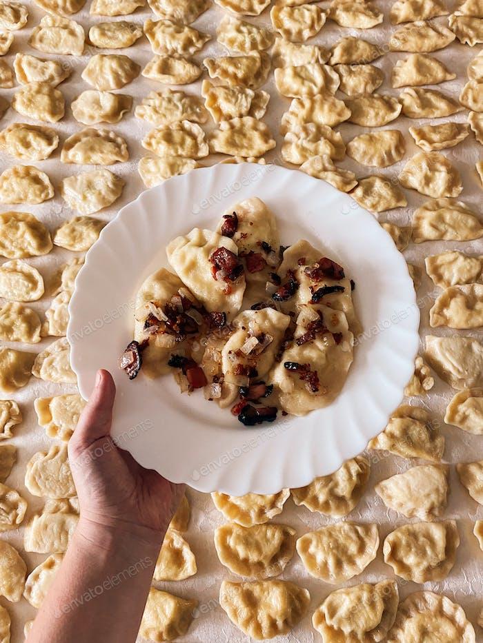 Freshly made pierogi, cooking, Polish food, dumplings, Polish dumplings, food from above, hand