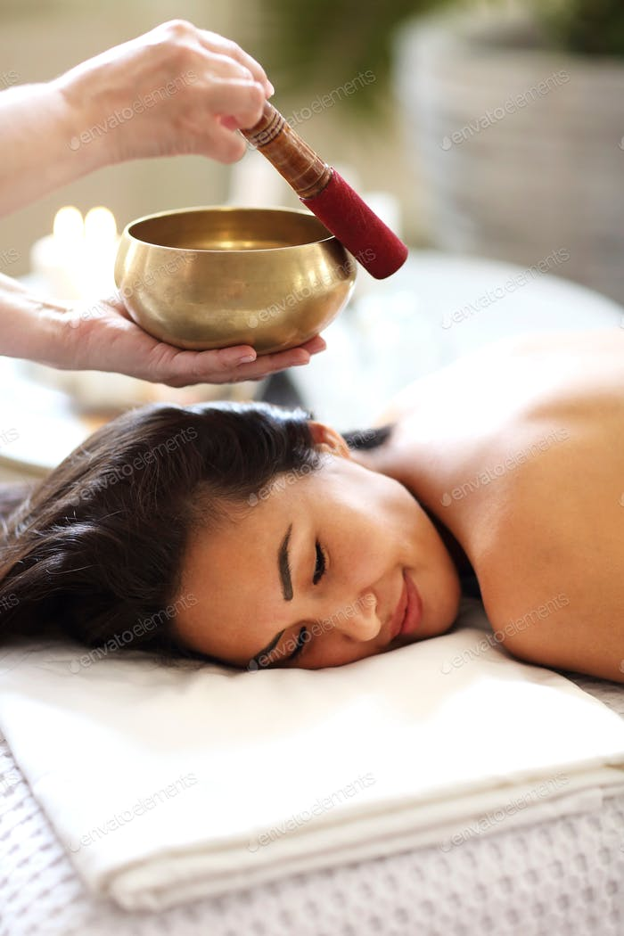 Diverse masseuse and client during sound therapy