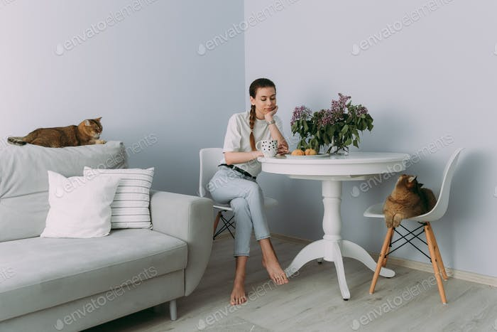 a young girl in a white t-shirt and jeans is sitting at a table and drinking tea at home in the