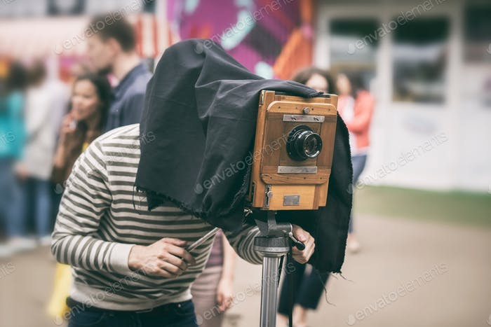 Photographer with antiquity vintage wooden camera under dark cloth cape photographing passers - old