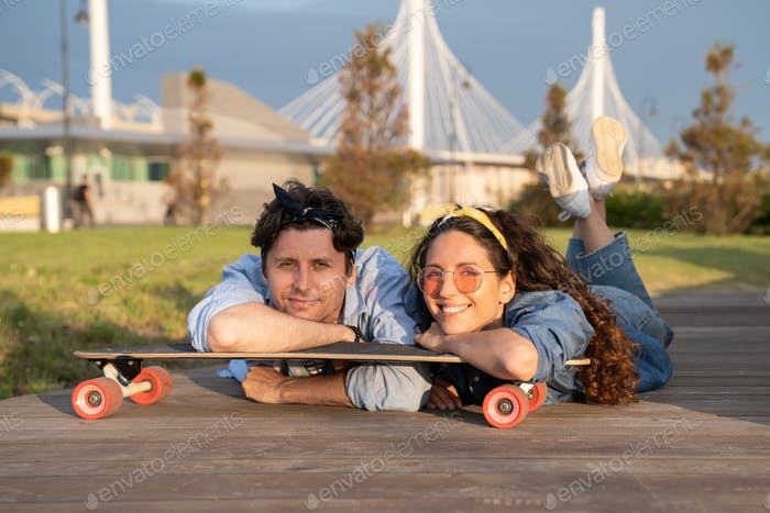 Young smiling couple chilling on longboard in city park at summer sunset. Urban lifestyle concept