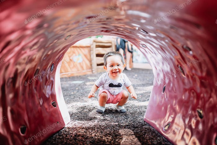 Diverse little boy playing outside playground outdoor fun happy cute smile.