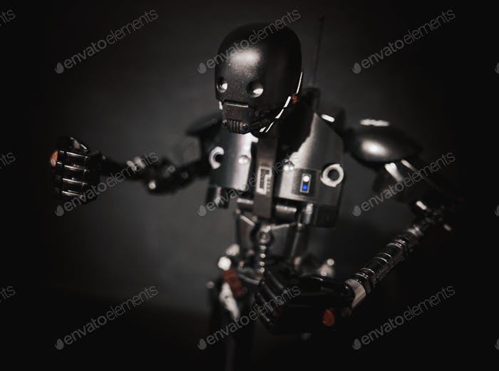 A lack robot toy in front of a black background. K2SO character from Star Wars.
