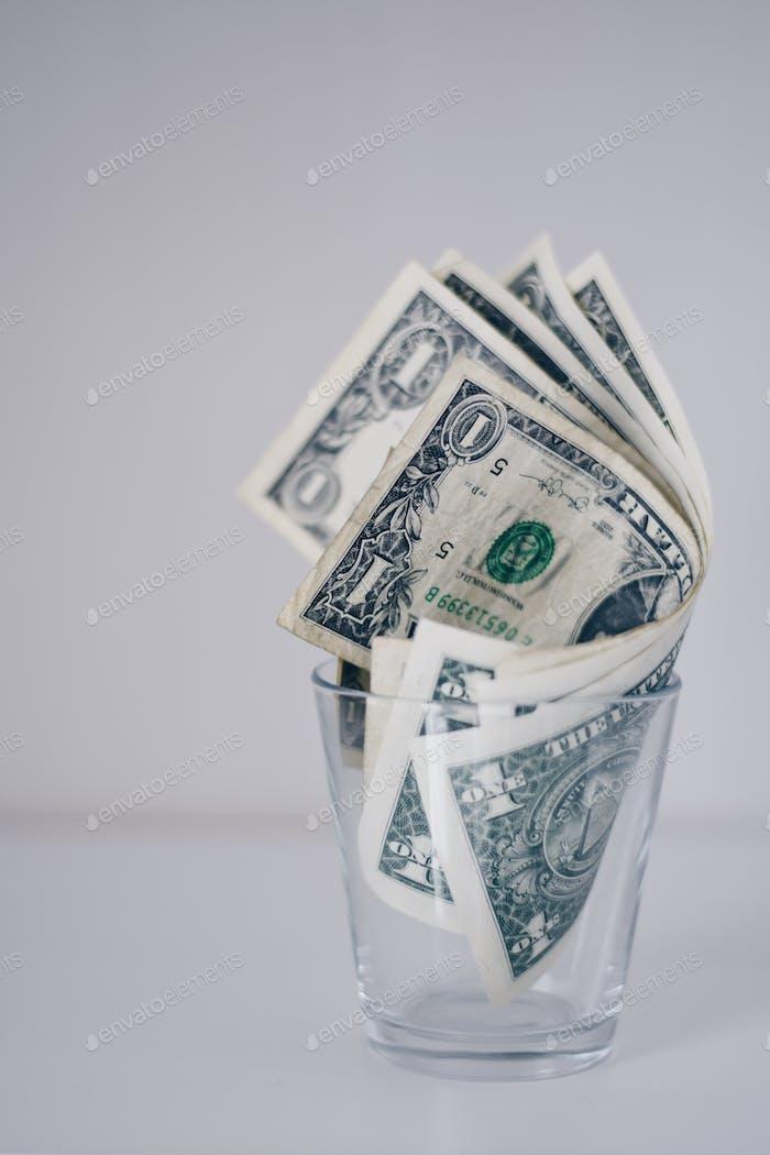 US-Papier-Dollar-Scheine in einem Glas
