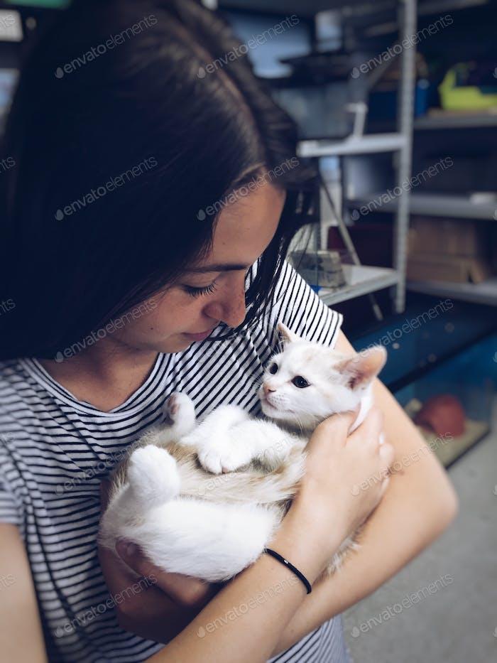 Молодая девочка-подросток держит милый маленький белый котенок в зоомагазине