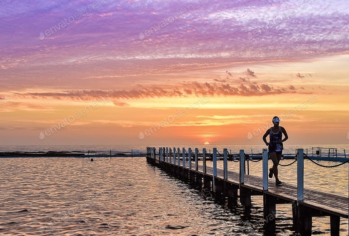 A jogger getting fit against a beautiful sunrise. Morning exercise along the pier