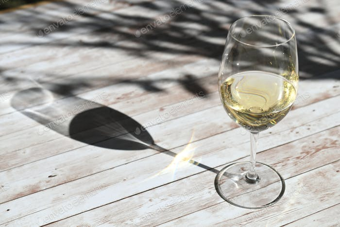Licht und Schatten - Weißwein im Weinglas mit geflecktem Sonnenlicht, das draußen durch Bäume gefiltert wird