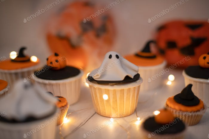 Halloween muffins with decorations in the form of ghosts, pumpkins and witch hats.