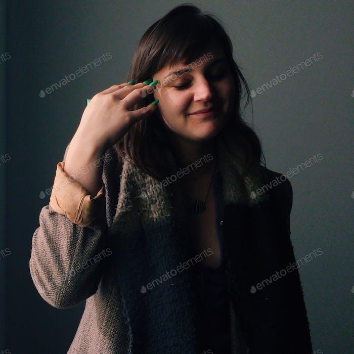 Женщина фиксирует волосы и делает смешное выражение.