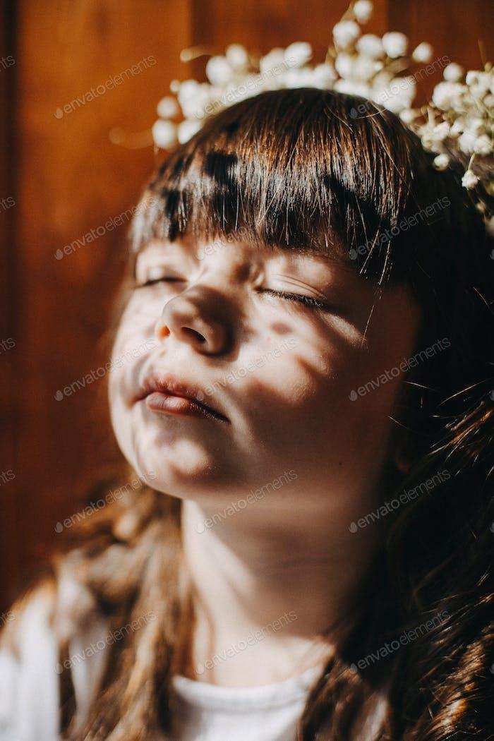 Baby Mädchen sitzt auf einem Balkon in den Strahlen der Sonne