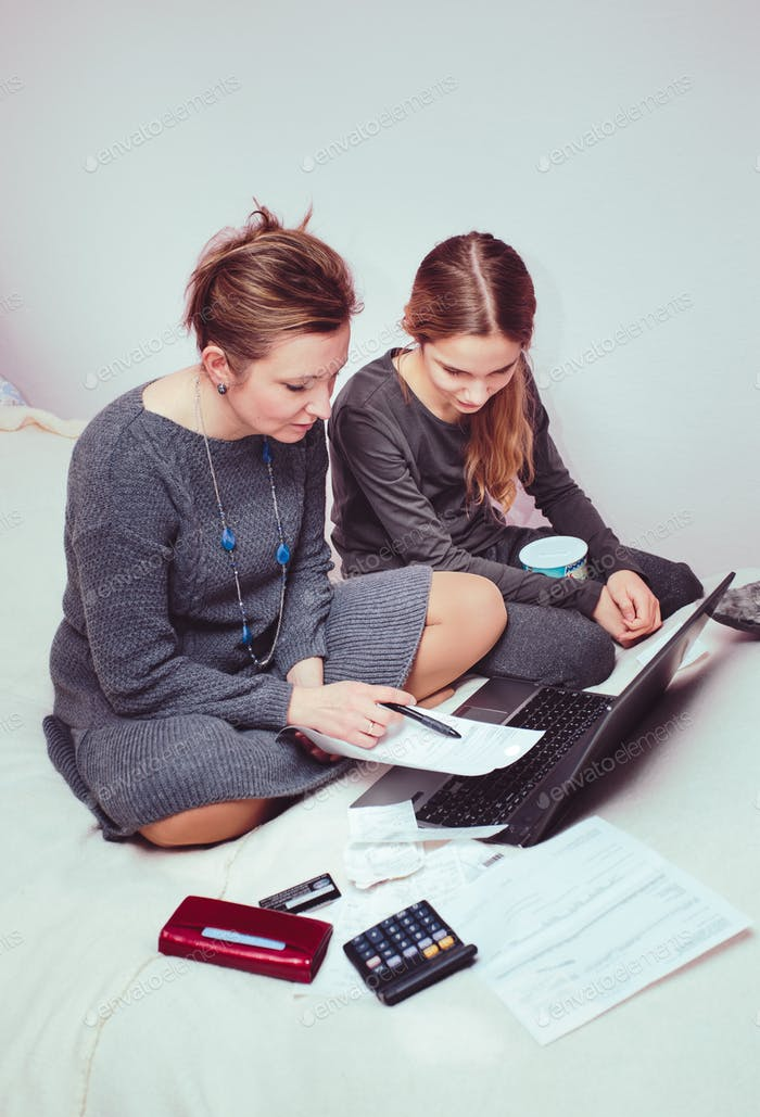 Woman and her daughter planning budget at home