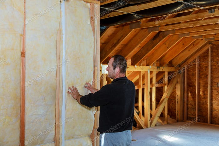 Worker thermally insulating a house attic using mineral wool installation of insulation in the house