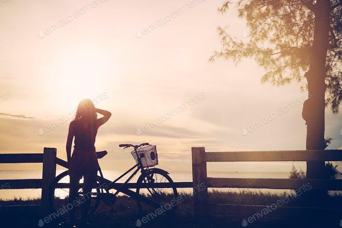 Ein Mädchen, das auf Sonnenaufgang/Sonnenuntergang mit einem Fahrrad schaut. Ein Volk von hinten.