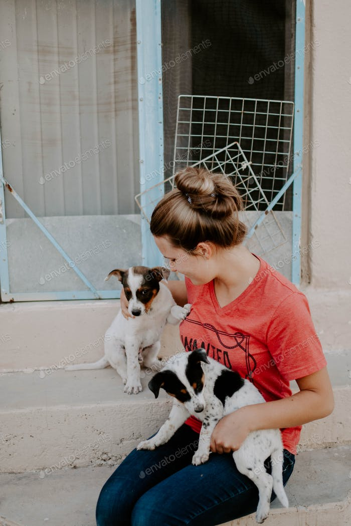 A girl playing with her new puppies.