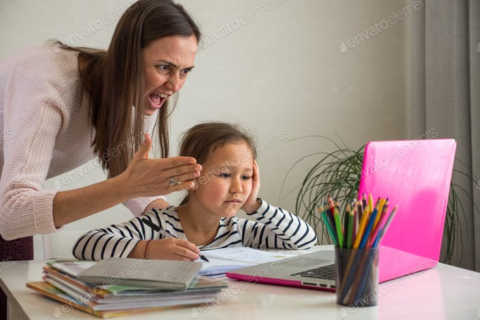 Furious adult woman screaming at laptop while helping tired ethnic girl to do homework assignment at