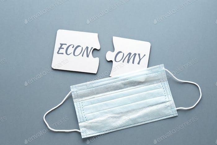 dos rompecabezas blancos con la palabra separada economía