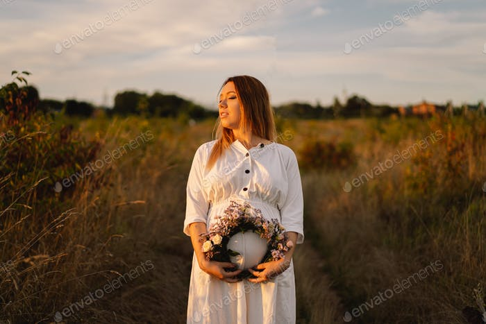Portrait of a pregnant woman. A beautiful young pregnant woman in a white dress walks in the field.