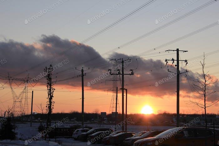 Telefonmasten und elektrische Leitungen bei Sonnenuntergang