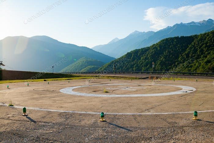 Helipad on the background of the mountain landscape at sunset.