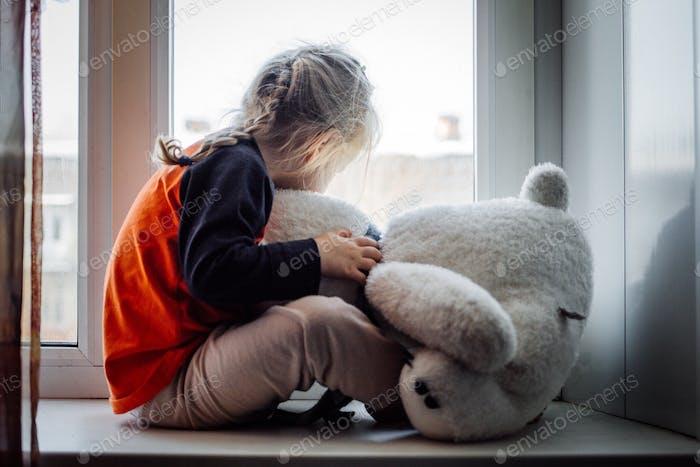 Sad little girl with a teddy bear Sadness