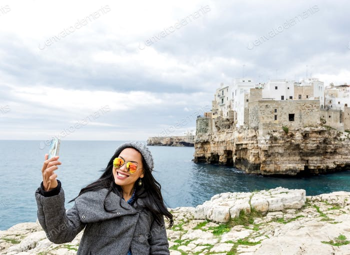 Tourist taking selfie with old town of Polignano a mare